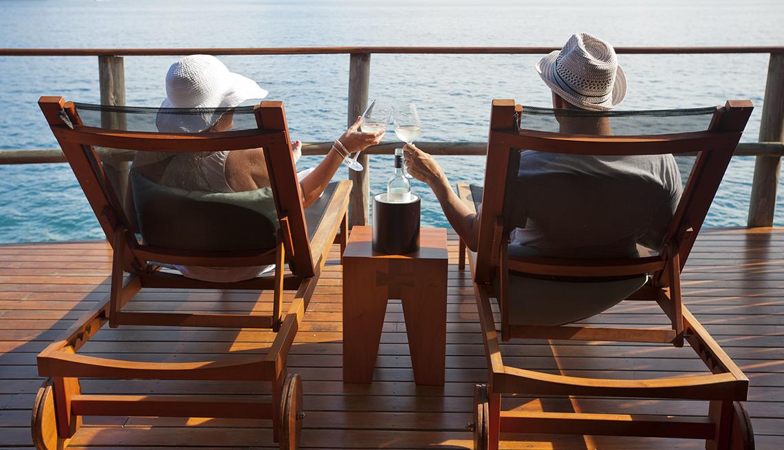 Pareja sentada mirando al océano desde un crucero - Fomas de ahorrar dinero con cupones