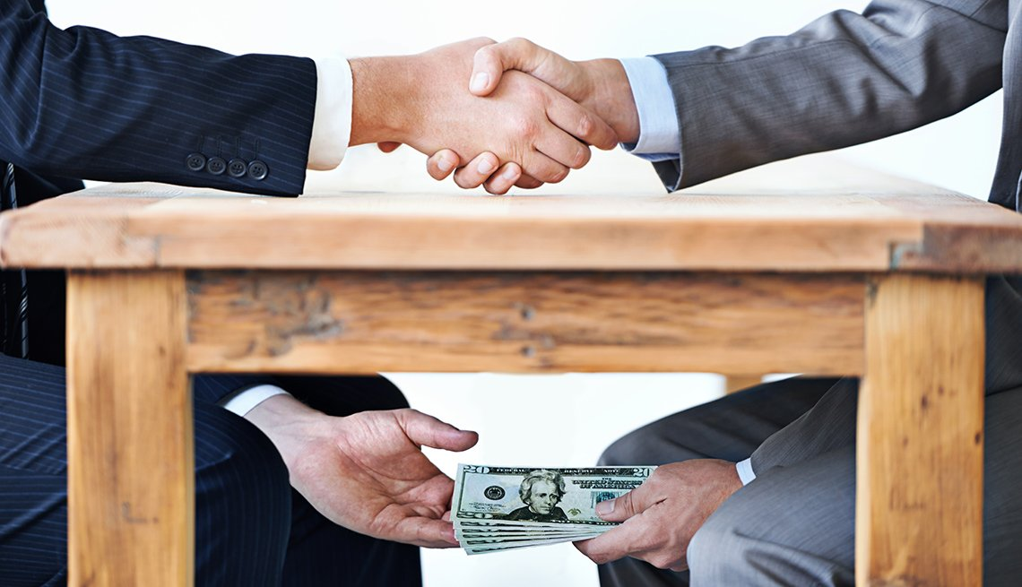 Men in suits shaking hands passing money under table