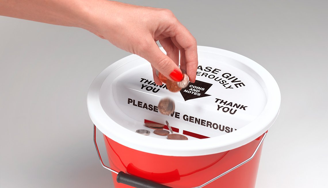 Hand putting change in collection bucket