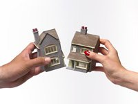 Man and woman holding toy house split in half.