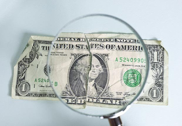 Dollar bill with magnifying glass