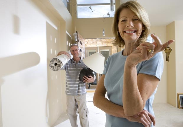 Mujer con las llaves de la casa y un hombre que se está mudando, Es malo avalar una hipoteca