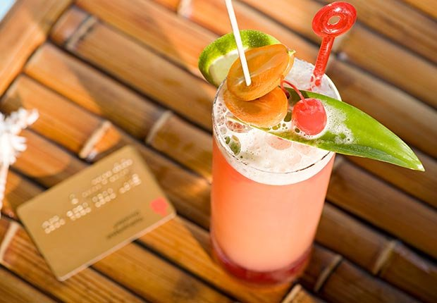 Cocktail and credit card (Image Source/Corbis)