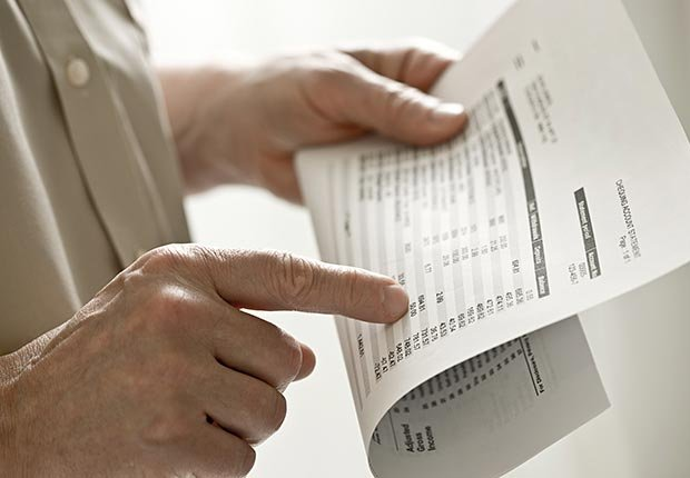 Man holding a bank statement (Image Source/Corbis)