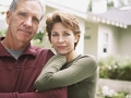 Couple standing in front of house. Why retirees can't get a mortgage.