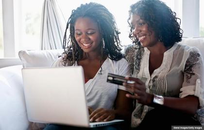 Madre e hija de compras en línea con una tarjeta de crédito. Ayude a sus hijos universitarios a usar bien sus tarjetas de crédito