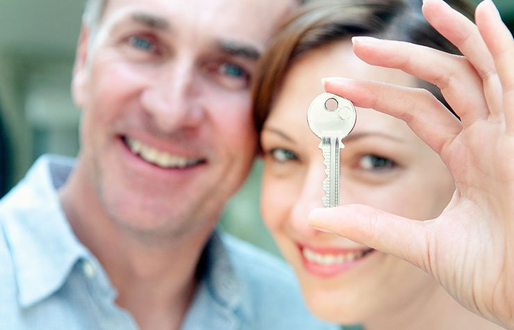 Woman holding a house key. Should you give your kids a mortgage?