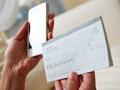 Mujer con un talonario de cheques y un teléfono inteligente en la mano - No page por los cargos extra de los bancos