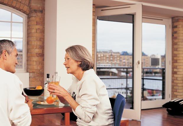 Pareja mayor cenando en casa. Tener mal crédito puede afectar sus perspectivas de empleo.