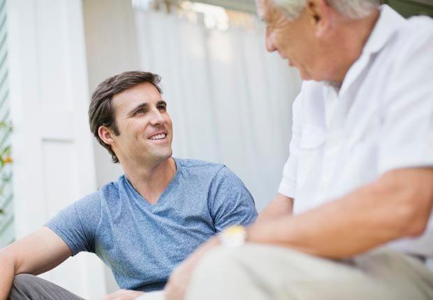 Hombre de mediana edad conversando con su padre. Tener mal crédito puede afectar sus perspectivas de empleo.