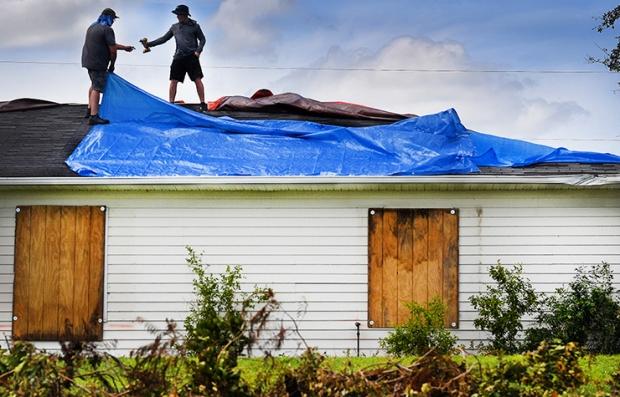 Dos personas reparando el techo de una casa después del paso del huracán