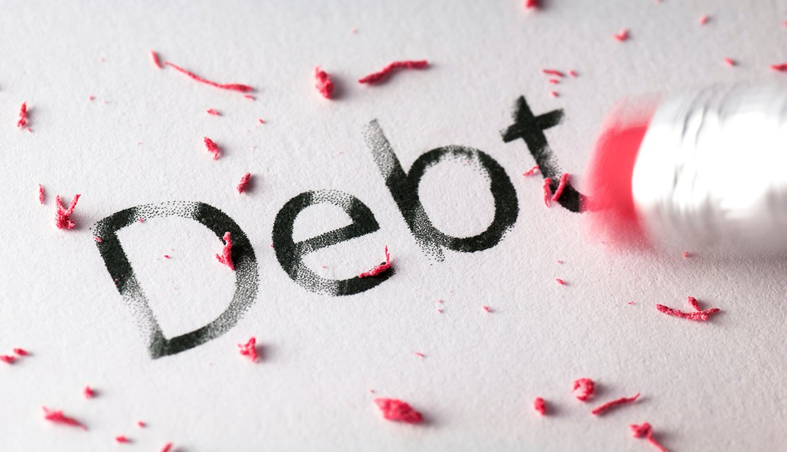 Palabra deuda escrita en inglés y un borrador de un lápiz pasando por encima, y libérate de deudas.