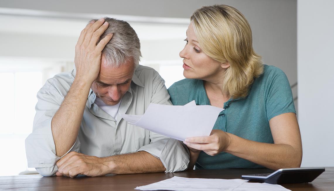 Una pareja mayor discutiendo por un documento que sostiene la mujer en la mano, mientras el hombre se lleva la mano a la cabeza