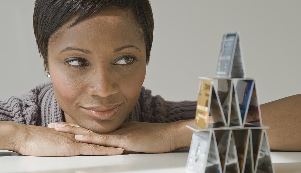Mujer mirando una pirámide de hecha con tarjetas de crédito y aprende de los secretos de estas compañías