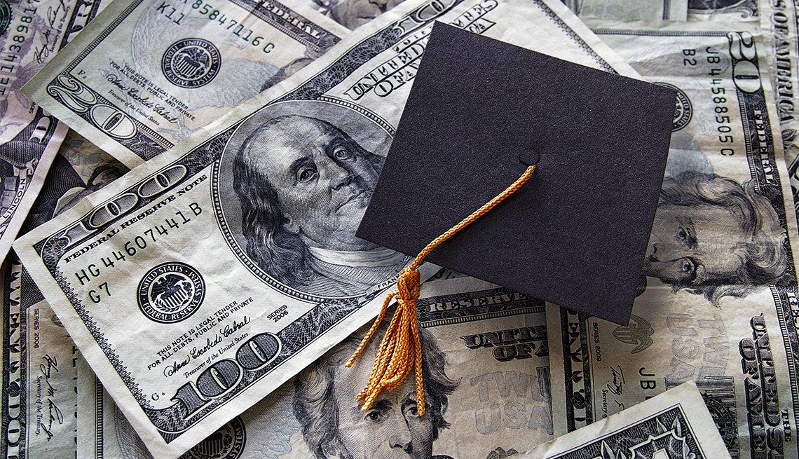 Sombrero de graduación pequeño sobre dinero en efectivo