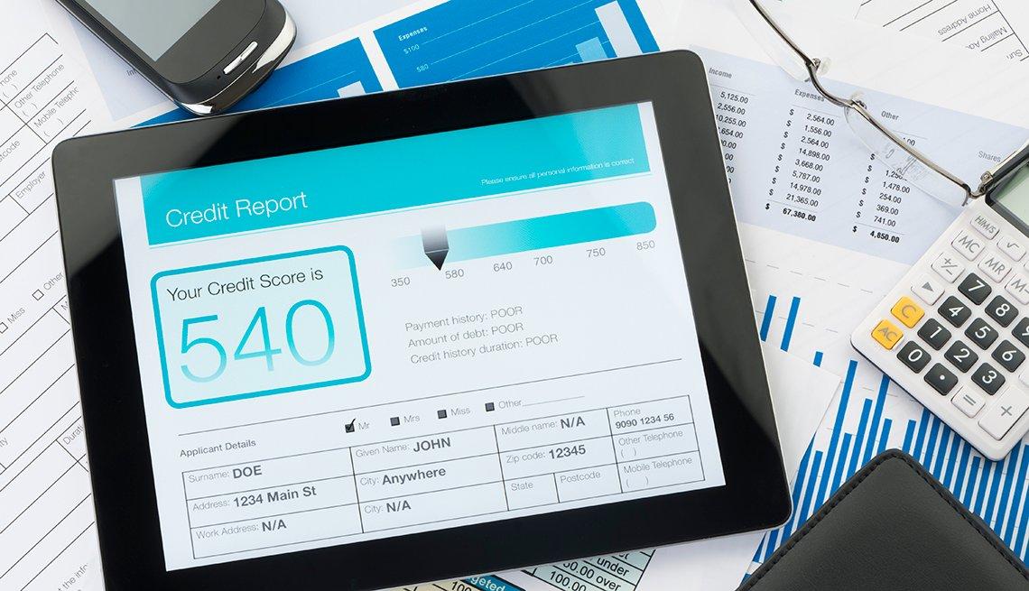 Reporte de crédito en una tableta sobre cuentas en papel.