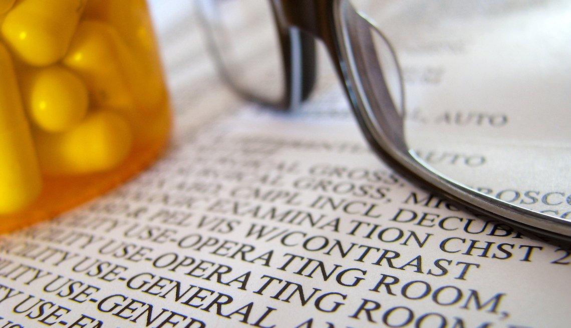 Factura de un hospital debajo de un frasco de medicinas y unas gafas.