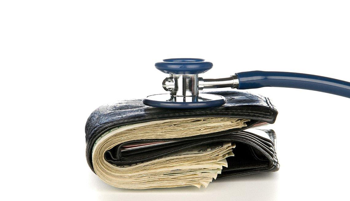 Billetera de cuero llena de dólares y un estetoscopio encima.