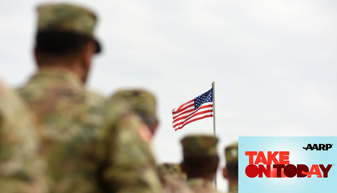 Soldiers standing in line with the American flag in the background.