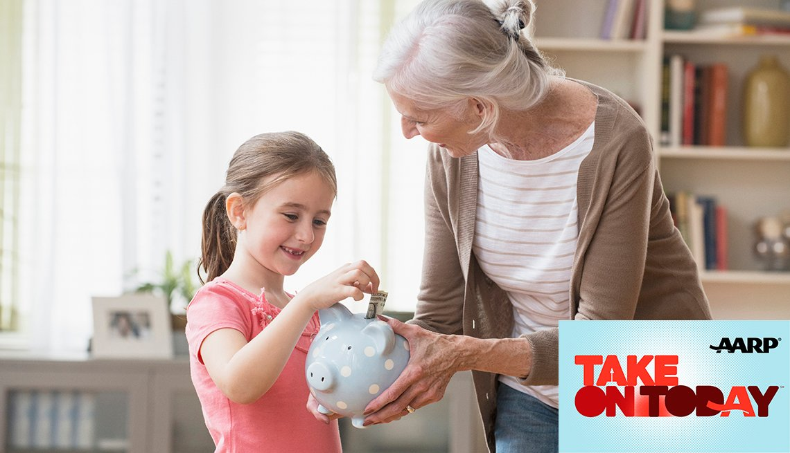 A young child puts money into a piggy bank that is being held by her grandmother