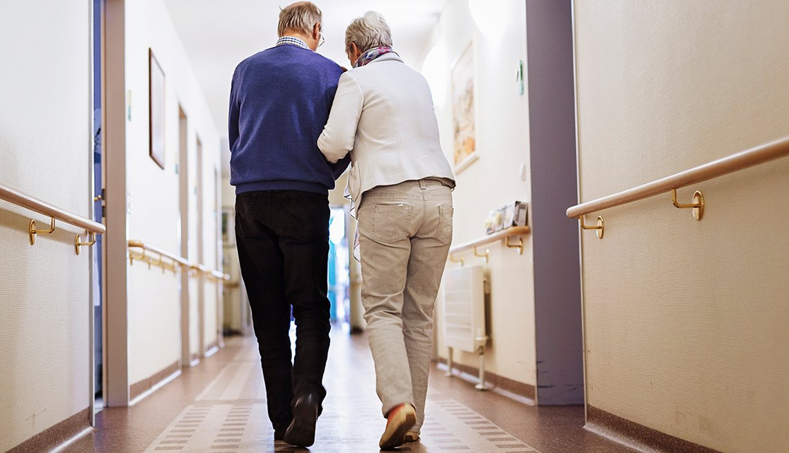 An older couple walking down the hall