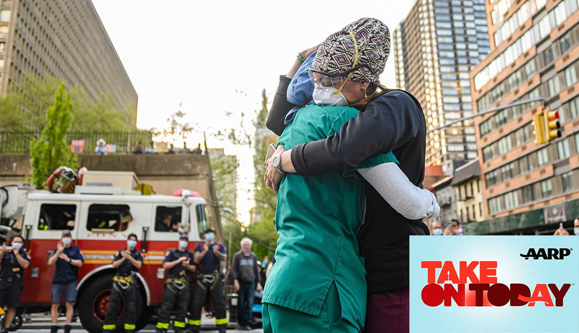 Two nurses hug outside of a hospital with firefighters applauding in the background