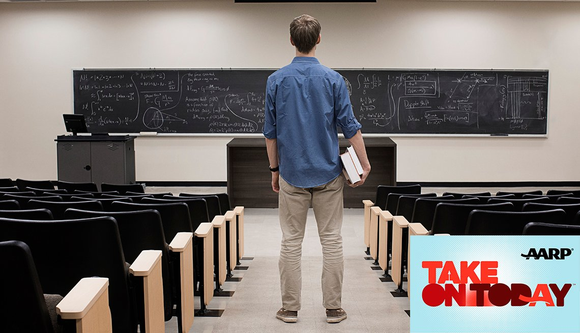 A man standing in an empty classroom