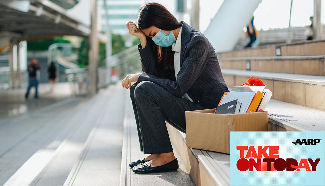 A woman sits on the steps with her head in her hands next to a box