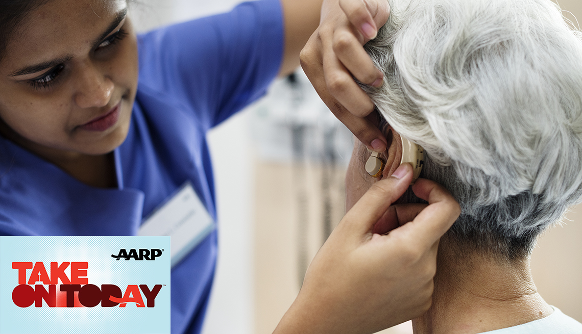 A person is putting on a hearing aid