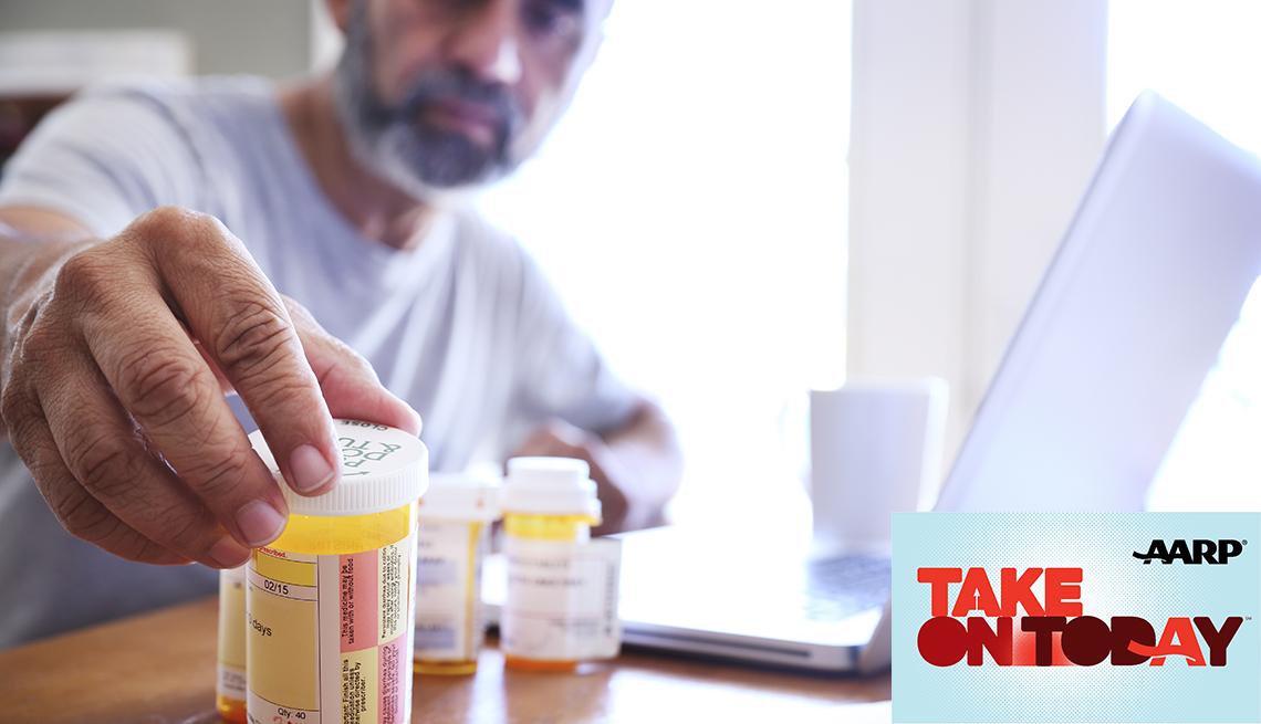 A man reaches for a bottle of pills