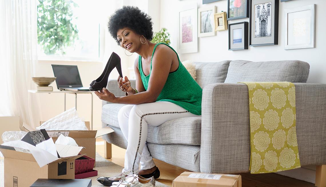 Mujer afroamericana abriendo una caja de zapatos en su sala