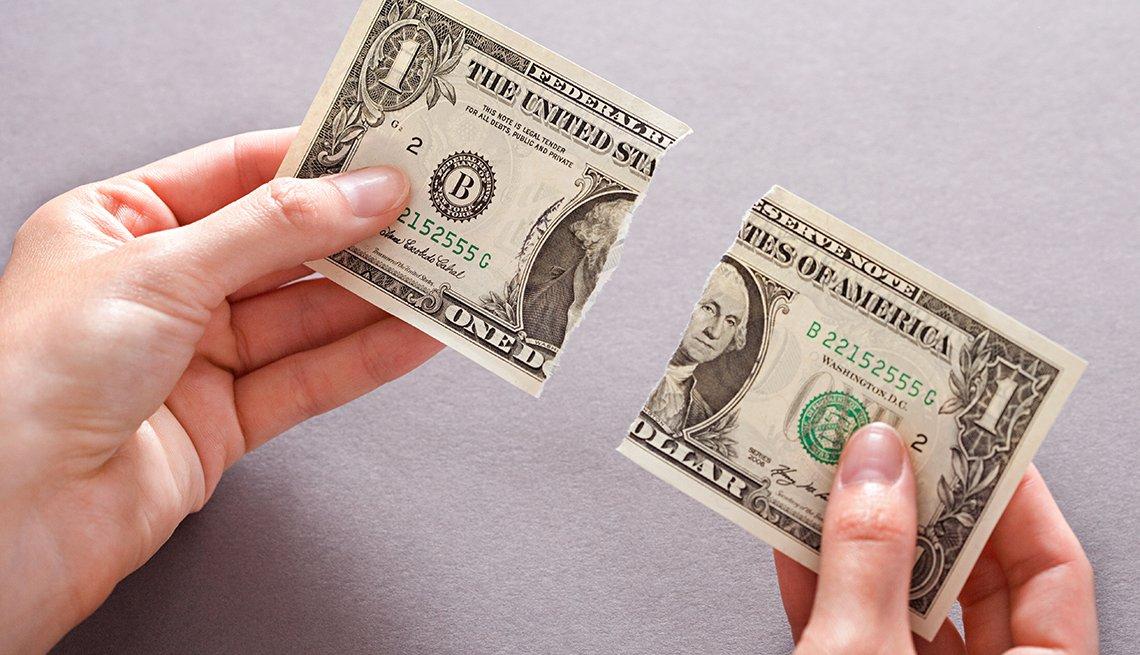 Manos sosteniendo billete de dólar rasgado a la mitad