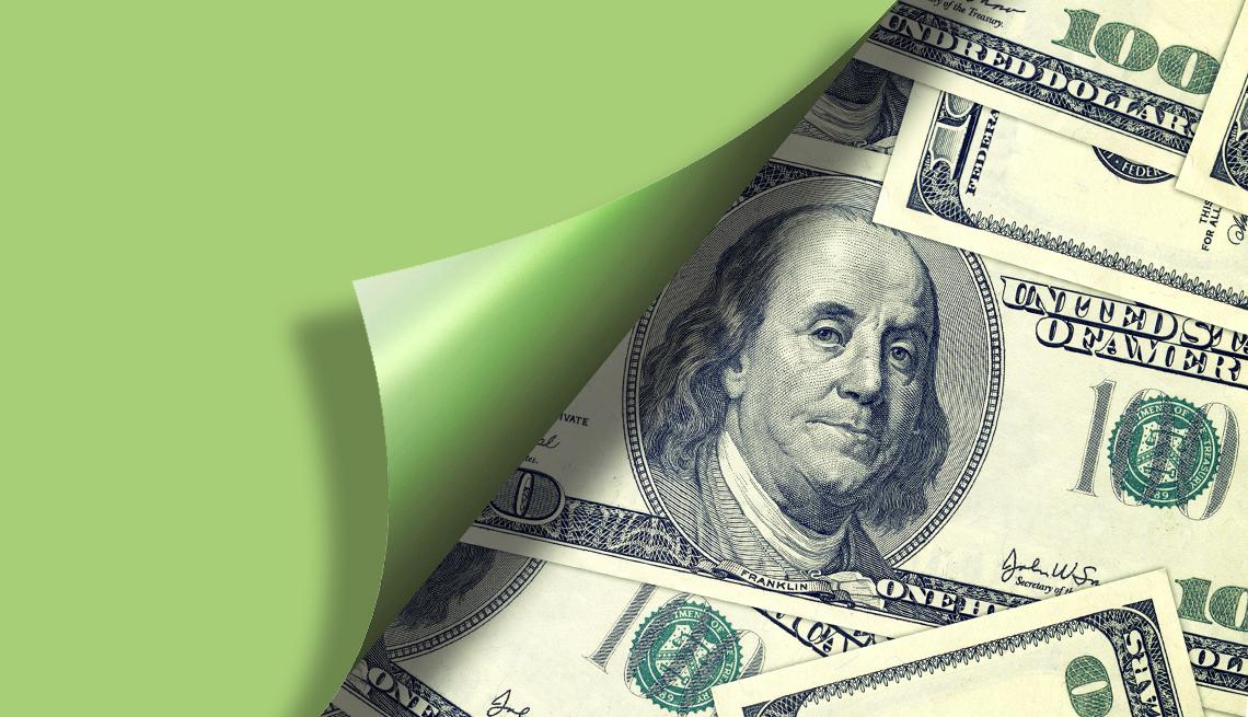 peeling back paper to reveal money