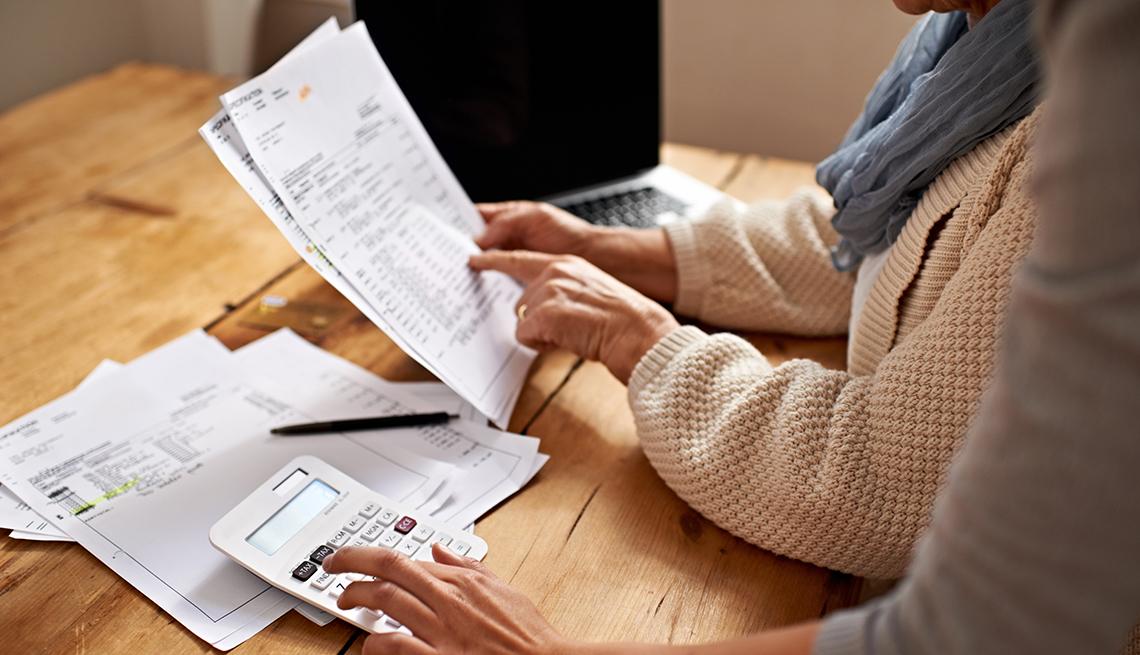 Manos de una mujer mayor viendo una factura y otra mano sobre una calculadora