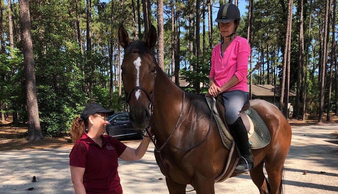 holly carter astride a rescued thoroughbred horse with another woman holding the bridle