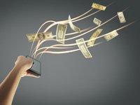 Una mano sostiene un teléfono inteligente y unas cuerdas con un flujo de dinero - Consejos para vender en línea seguramente