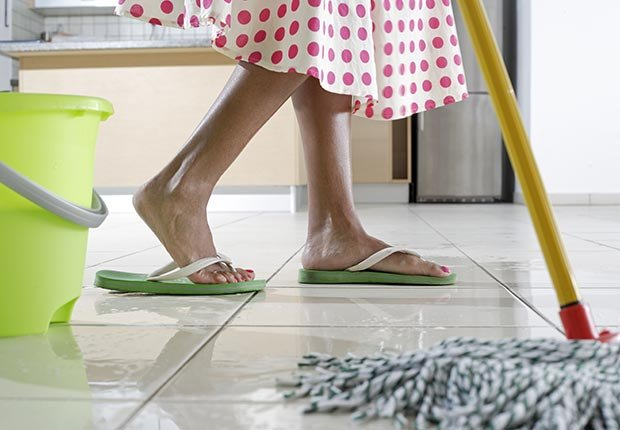 Feet of woman mopping kitchen