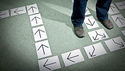 Pies de un hombre con flechas en el piso, Elegir el camino más seguro de Inversión