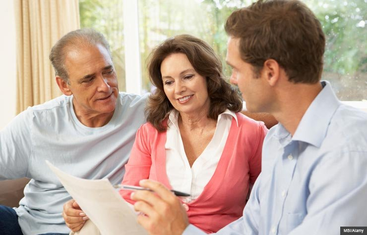 Senior couple at home with a financial advisor. (MBI/Alamy)