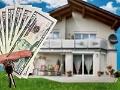 Billetes de 10 dólares sostenidos por una mano y las llaves de una casa que se muestra al fondo para ilustrar el negocio de los bienes raíces