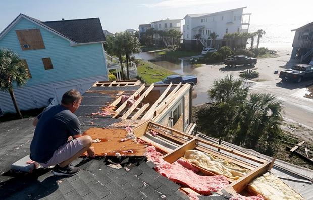 Hombre reparando el techo de una casa después del paso de los huracanes.