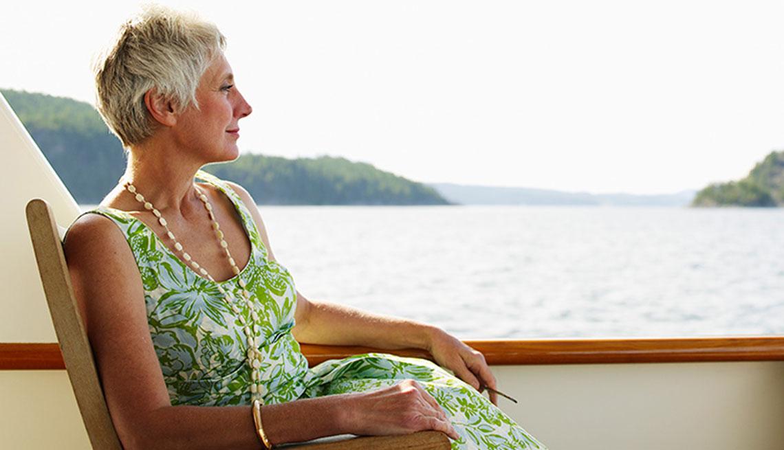 Mujer en un crucero, sentada y mirando al agua
