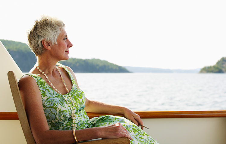 A woman on a cruise looks out on the water