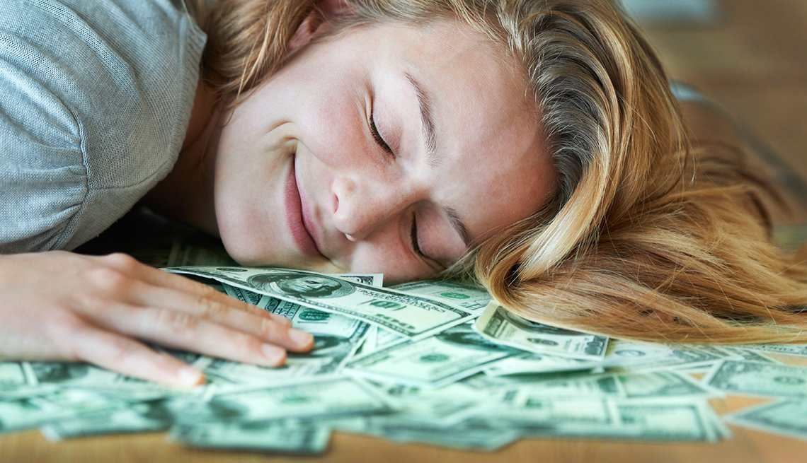 a woman happy and resting on money