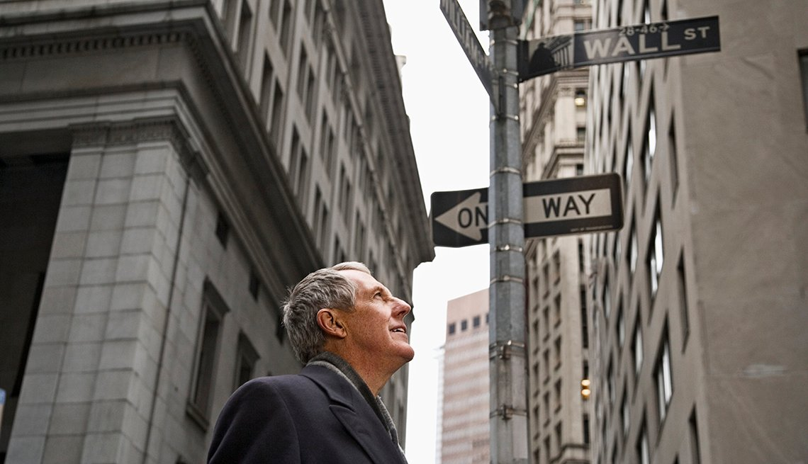 Man looking up at Wall Street sign in NYC