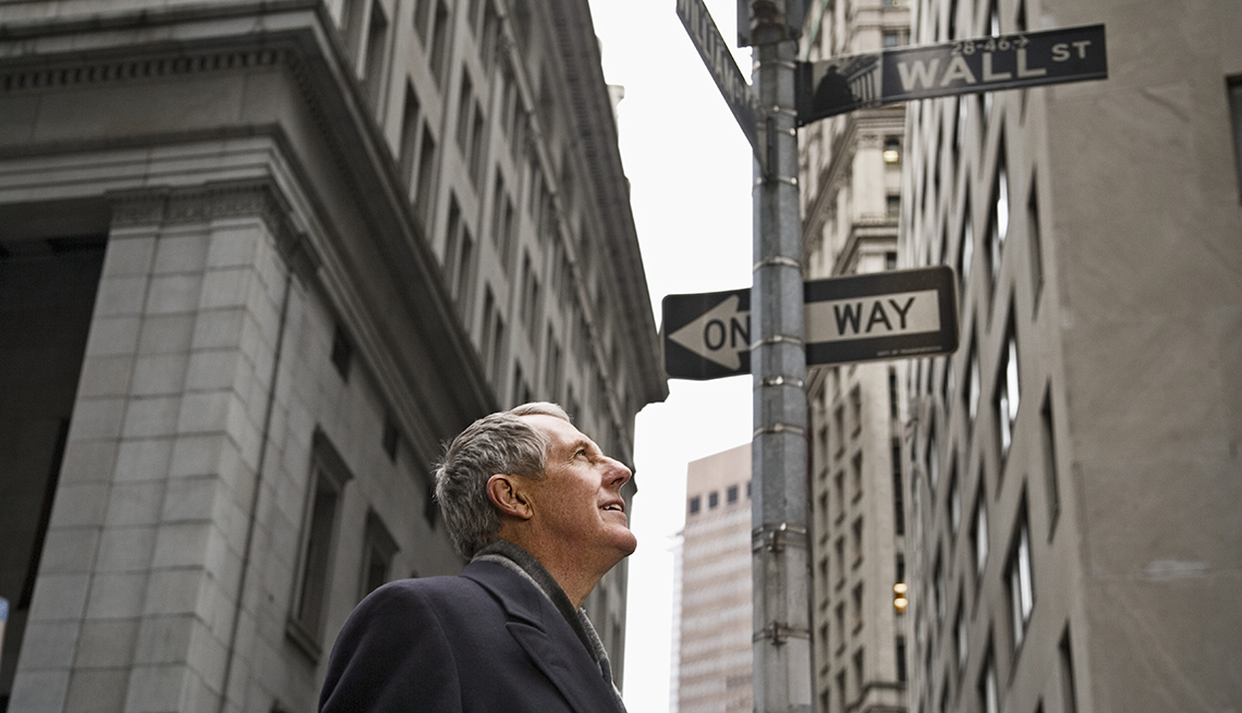 item 1 of Gallery image - Man looking up at Wall Street sign in NYC