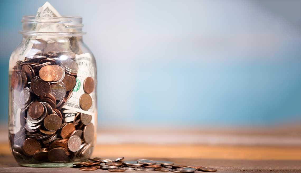 Jarra de vidrio con monedas y dólares dentro.
