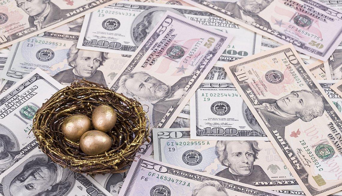 Nido con huevos de oro encima de una superficie llena de dólares.