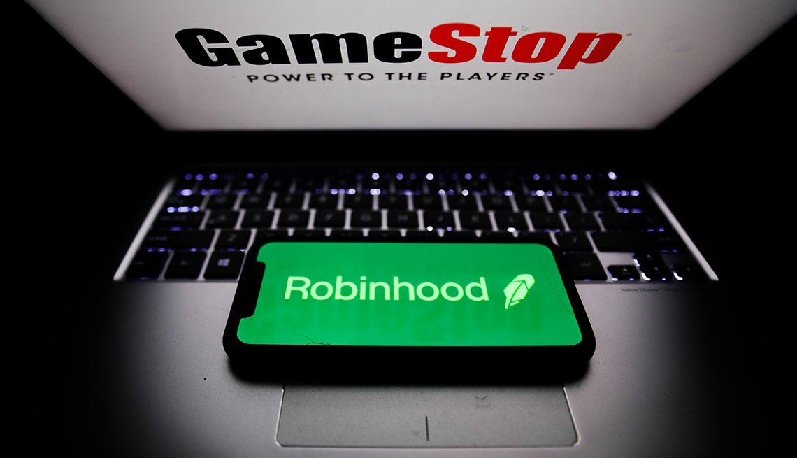 Robinhood stock trading app logo displayed on a phone screen and GameStop logo displayed on a laptop screen