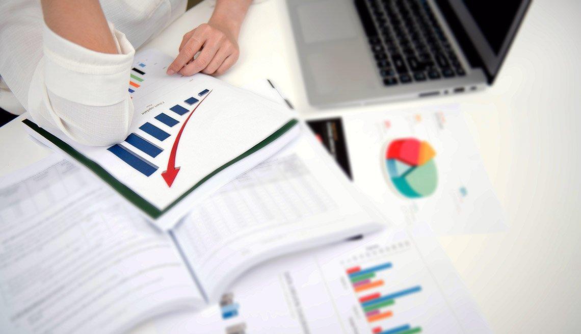 Mujer en su escritorio analizando cuadros de finanzas